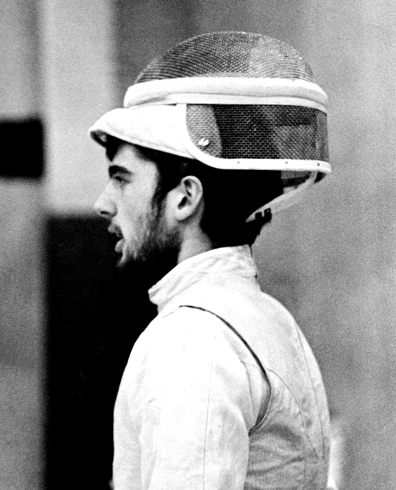 A black and white photo of Rocky as a younger man, in his fencing gear, with is mask up and balanced on the top of his head, looking away from the camera.